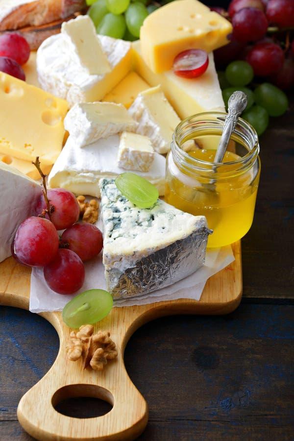 Diversos tipos de queso con las uvas, la miel y las nueces en tabla de cortar imagen de archivo libre de regalías