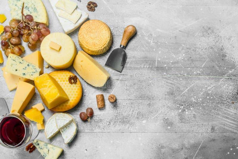 Diversos tipos de queso con las uvas, las nueces y un vidrio de vino tinto fotografía de archivo