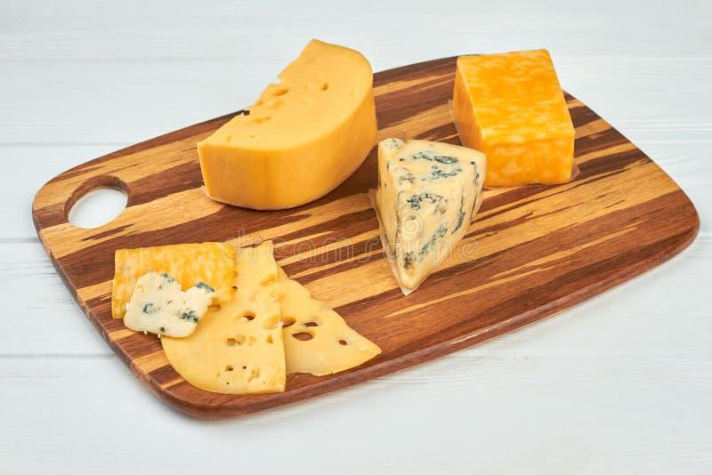 Diversos tipos de queso en el tablero de madera imagenes de archivo