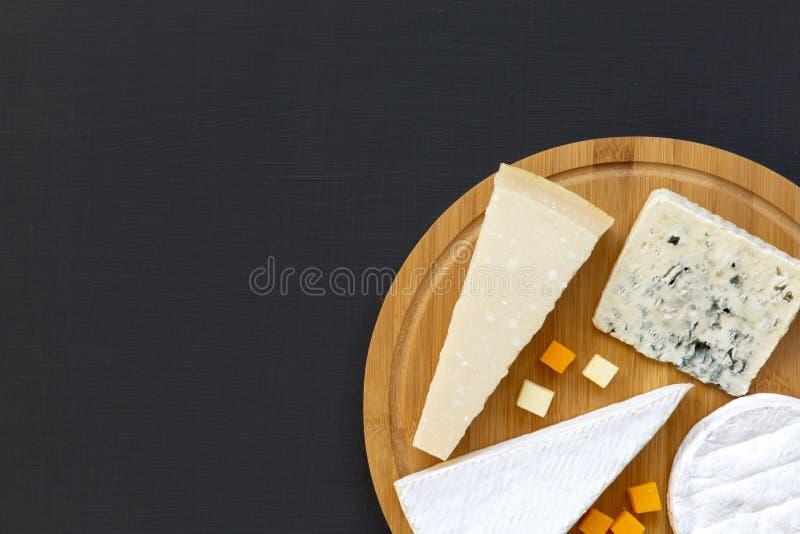 Diversos tipos de queso en el tablero de madera redondo, visión superior Fondo oscuro Copie el espacio fotografía de archivo