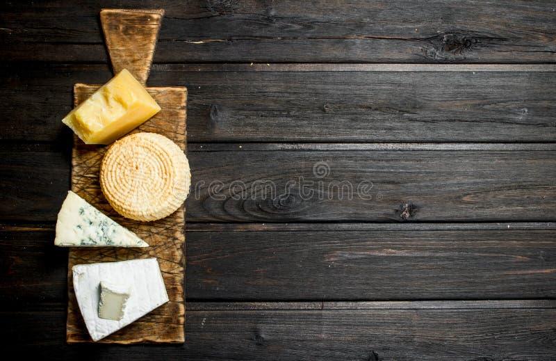 Diversos tipos de queso en la tabla de cortar foto de archivo libre de regalías
