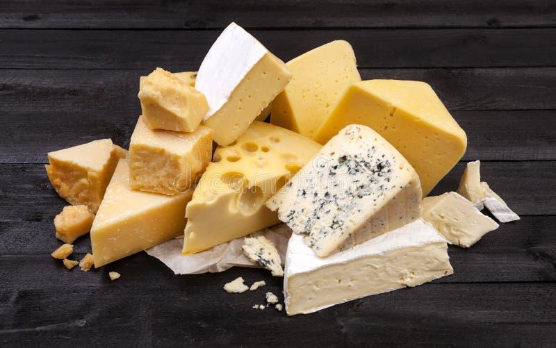 Diversos tipos de queso en la tabla de madera negra imagenes de archivo