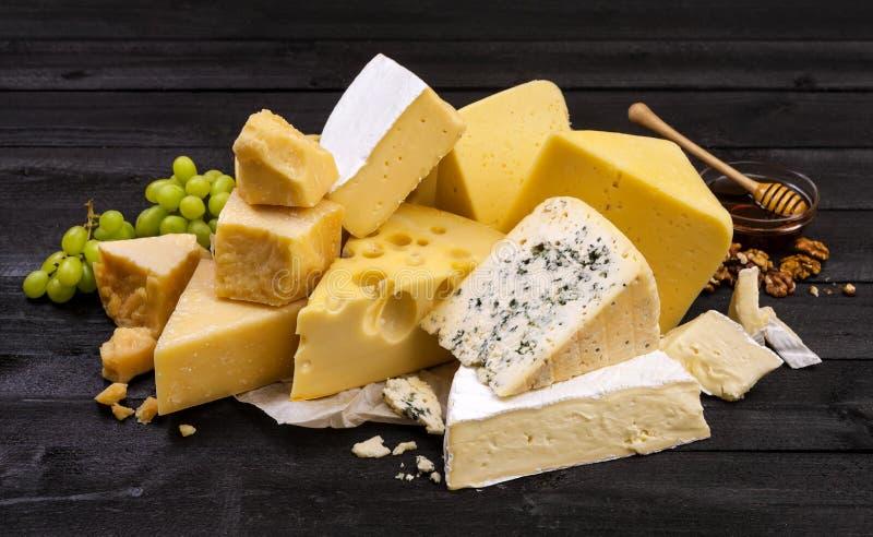Diversos tipos de queso en la tabla de madera negra fotografía de archivo