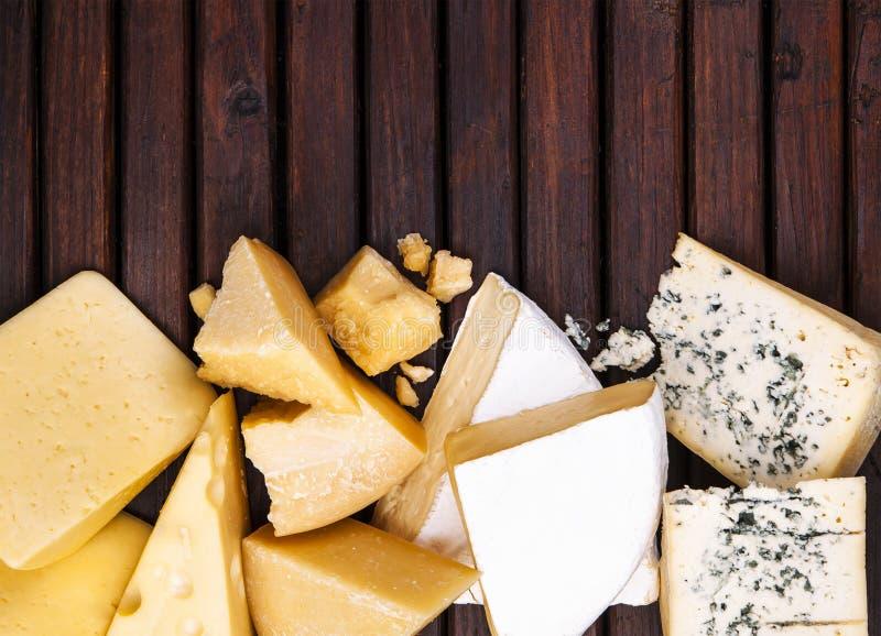 Diversos tipos de queso en la tabla de madera, visión superior foto de archivo libre de regalías