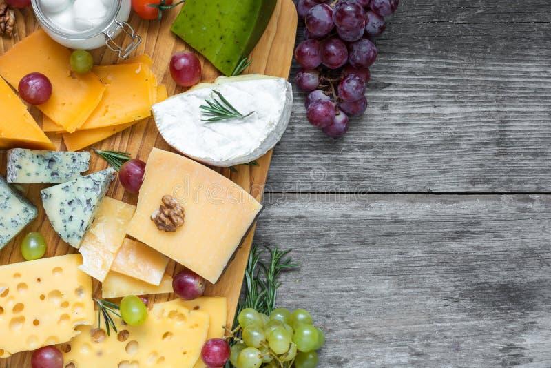 Diversos tipos de queso en tabla de cortar con la uva y las nueces sobre la tabla de madera rústica, visión superior imagen de archivo
