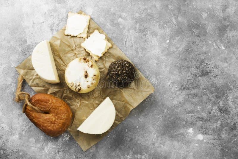 Diversos tipos de queso en un fondo gris Visión superior, balneario de la copia foto de archivo