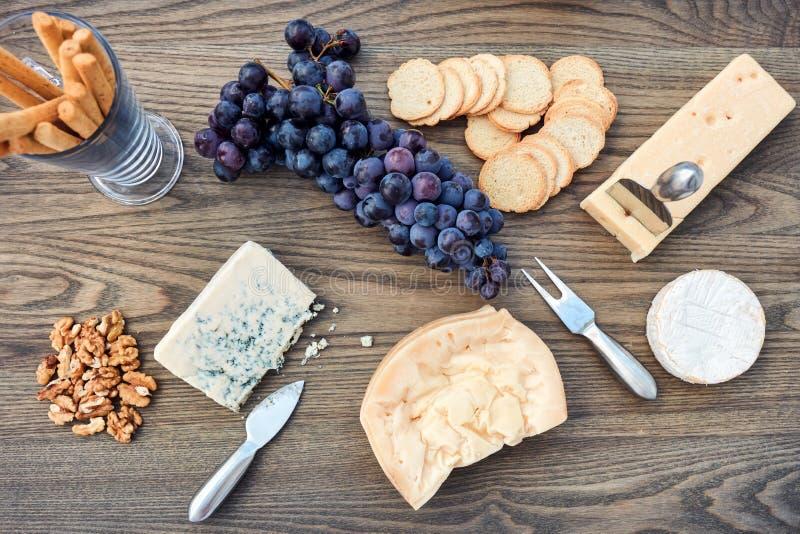 Diversos tipos de queso de lujo en el disco de madera del queso foto de archivo