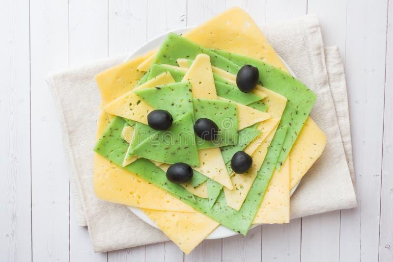 Diversos tipos de queso se cortan en una placa con las aceitunas fotografía de archivo