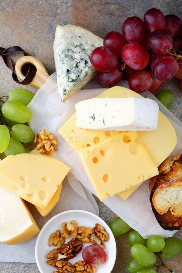 Diversos tipos de quesos de la charcutería con las uvas, el pan y las nueces en el fondo de la pizarra imagen de archivo