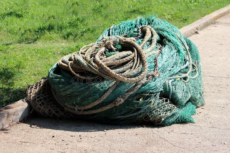 Diversos tipos de redes de pesca muy usadas y cuerdas fuertes con las cadenas aherrumbradas en una pila grande en el borde de la  imagenes de archivo