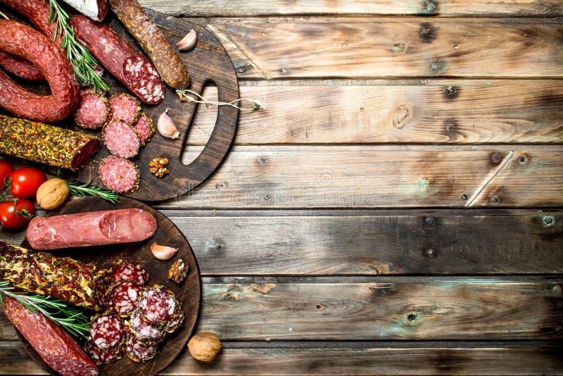 Diversos tipos de salami en un tablero con las nueces fotos de archivo