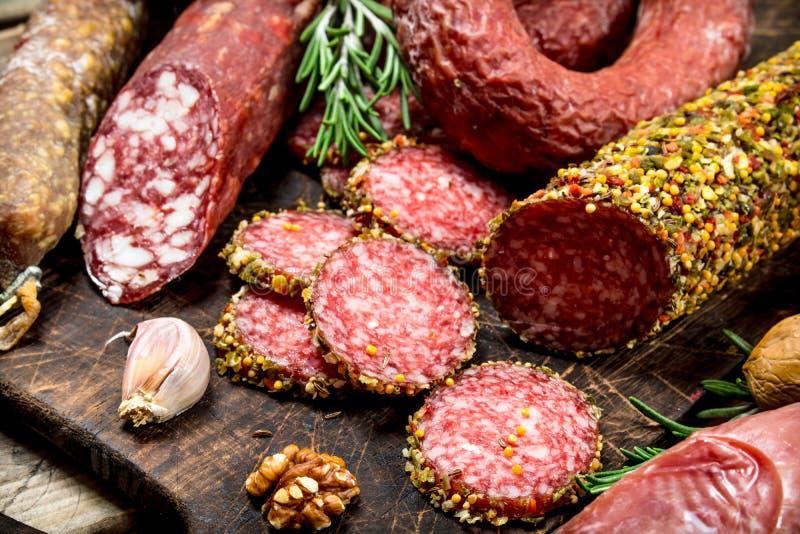 Diversos tipos de salami en un tablero con las nueces fotografía de archivo