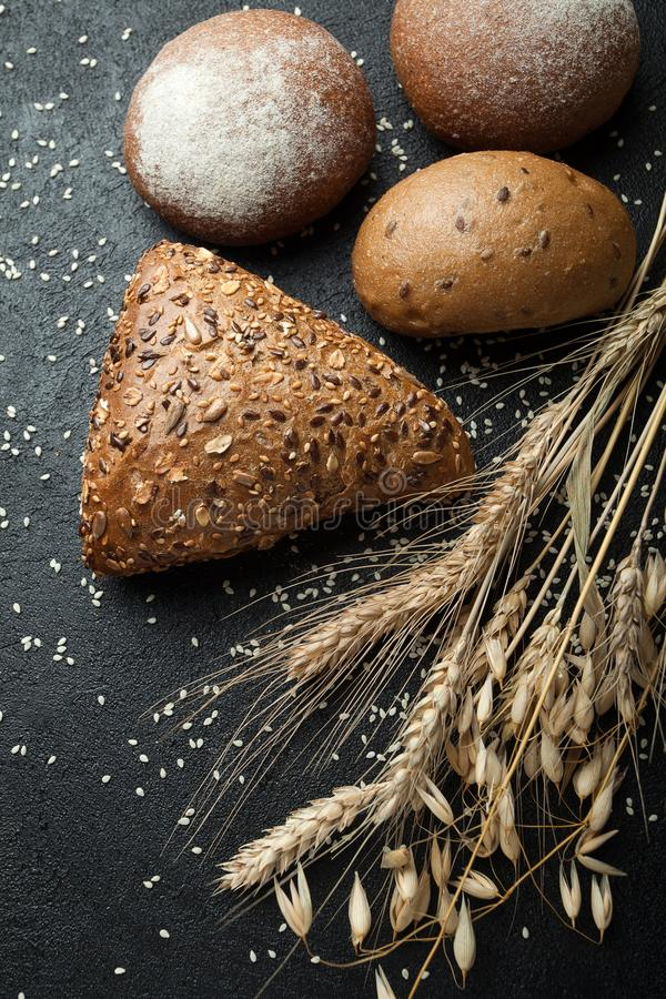 Diversos tipos hechos en casa de pan en un fondo oscuro rústico imagenes de archivo