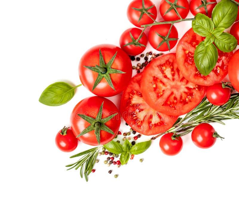 Diversos tomates coloridos con las hojas, las hierbas y las especias de la albahaca aisladas en el fondo blanco Endecha plana Vis imagenes de archivo