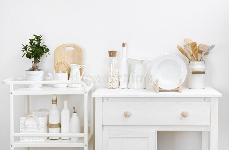 Diversos utensilios y dishware de la cocina con muebles elegantes del blanco del vintage foto de archivo