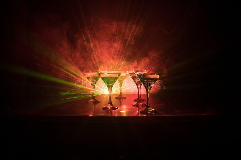 Diversos vidros do cocktail famoso Martini, tiro em uma barra com luzes nevoentas tonificadas escuras do fundo e do disco Conceit foto de stock