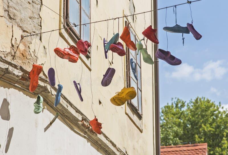 Diversos zapatos que cuelgan de un cable imagenes de archivo