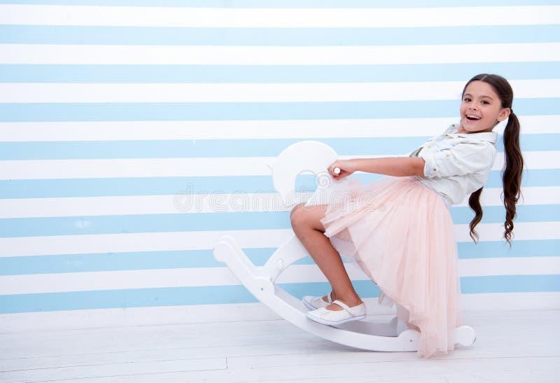 Diverta Il bambino della ragazza monta il cavallo a dondolo bianco su fondo a strisce Fronte felice della ragazza del bambino con immagine stock