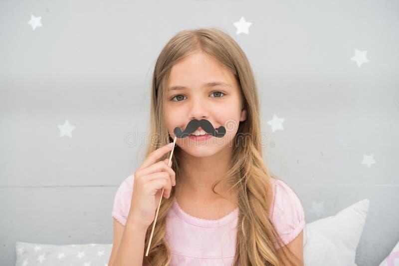 Divertendosi con i baffi falsi Concetto di umore e di felicità Fronte felice di sorriso dei capelli lunghi del bambino Bambino sp fotografie stock
