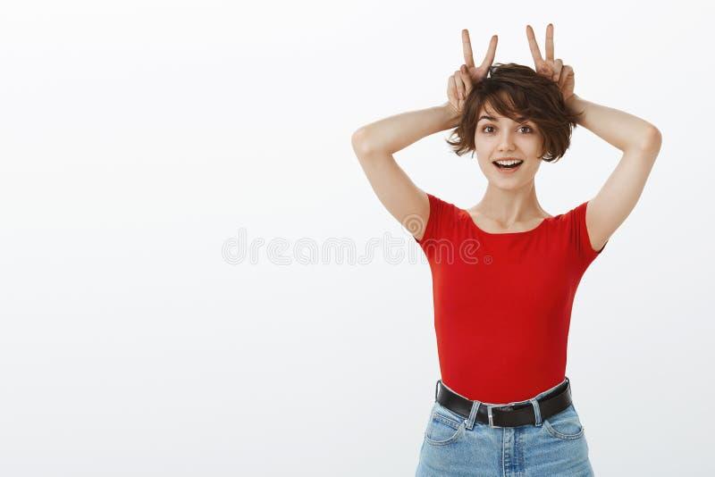 Divertente, sciocca ragazza europea carina e carina, con capelli corti e capelli color folcino, orecchie di coniglio reggono i ca immagini stock libere da diritti