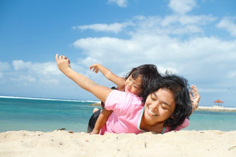 Divertimento étnico da criança com a matriz na praia tropical fotografia de stock royalty free