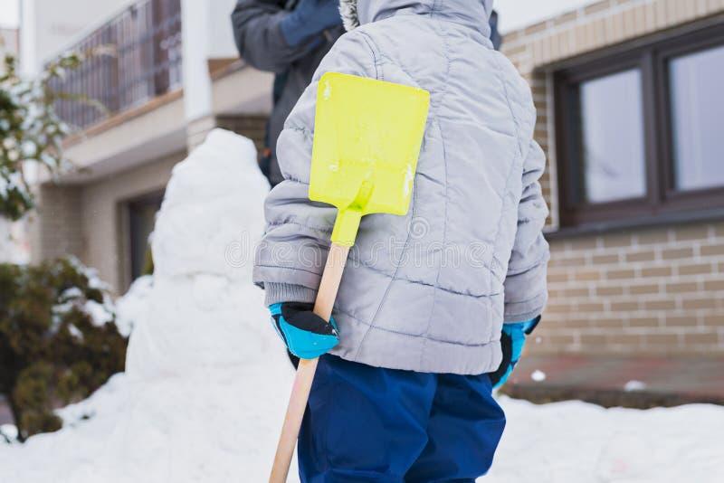Divertimento autentico di inverno della famiglia Famiglia che costruisce un pupazzo di neve nel loro frontyard Immagine reale sch fotografia stock libera da diritti
