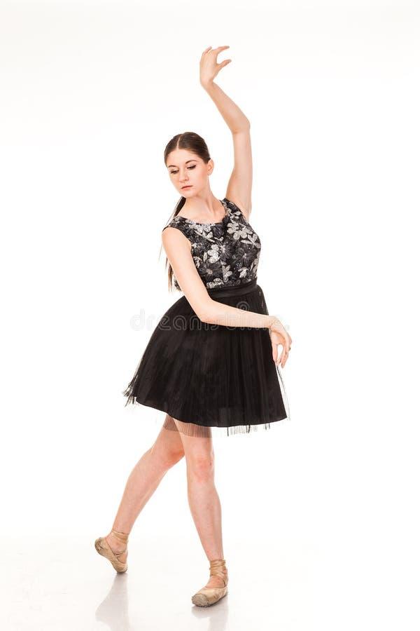 Divertimento bonito da dança da menina na câmera, levantando contra o fundo branco fotografia de stock royalty free