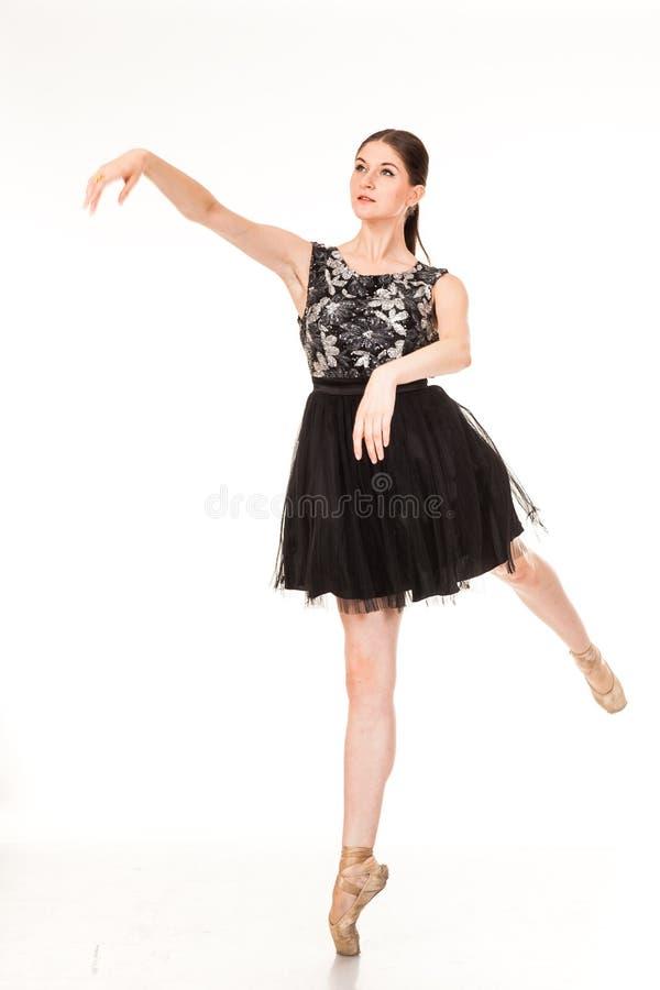 Divertimento bonito da dança da menina na câmera, levantando contra o fundo branco fotografia de stock