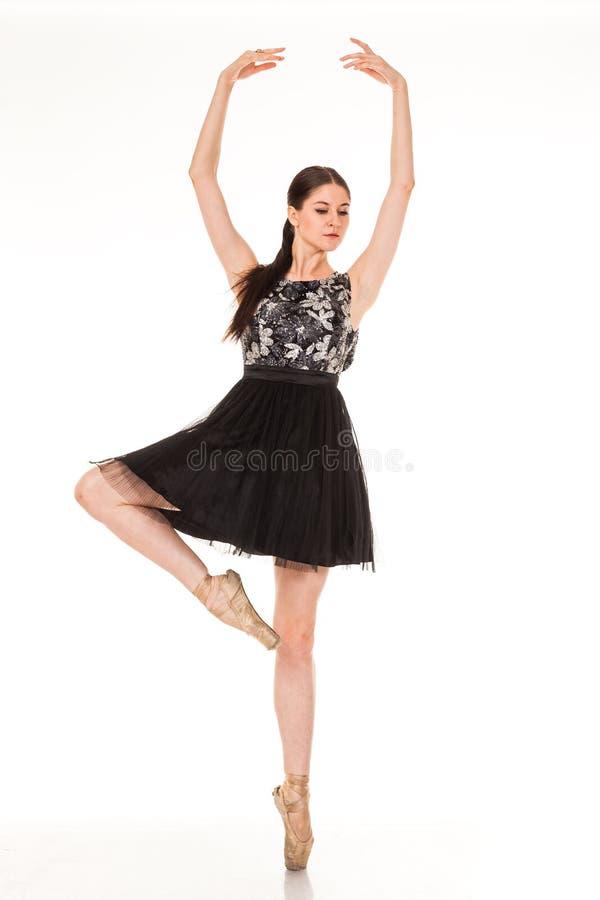 Divertimento bonito da dança da menina na câmera, levantando contra o fundo branco imagem de stock