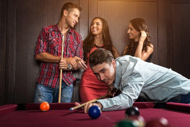 Divertimento com os amigos durante o jogo do bilhar foto de stock