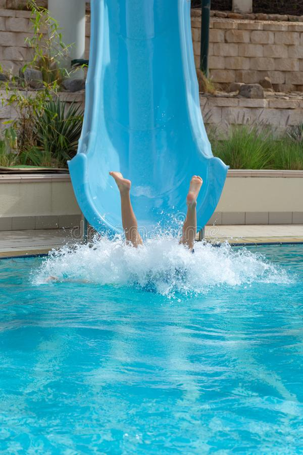 Divertimento da corrediça de água na piscina no verão que deixa de funcionar na água que faz um respingo grande imagens de stock