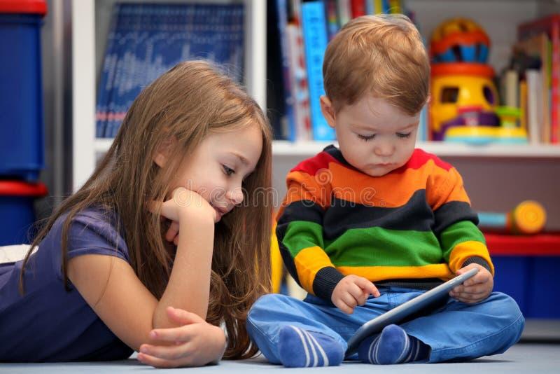 Divertimento da menina e do irmão usando um tablet pc digital imagens de stock royalty free
