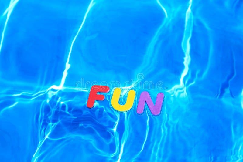 DIVERTIMENTO da palavra que flutua em uma piscina imagens de stock