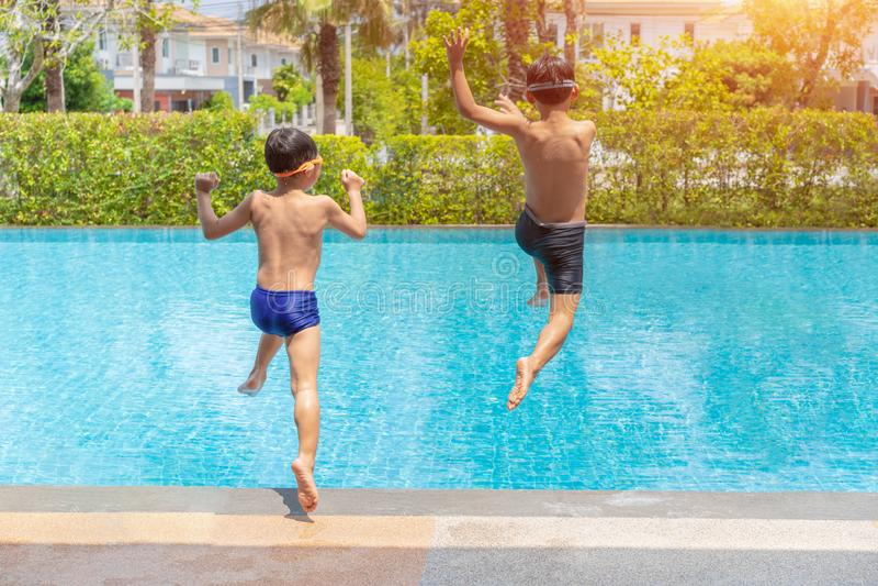 Divertimento de dois rapazes pequenos que salta na piscina, nas férias de verão e no conceito das férias fotografia de stock
