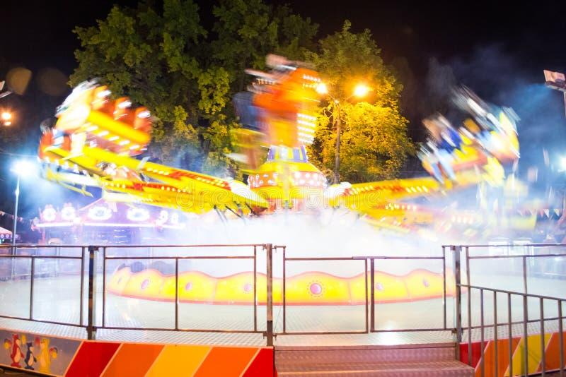 Divertimento del carosello alla notte nel parco, con un moto vago, esposizione lunga fotografia stock