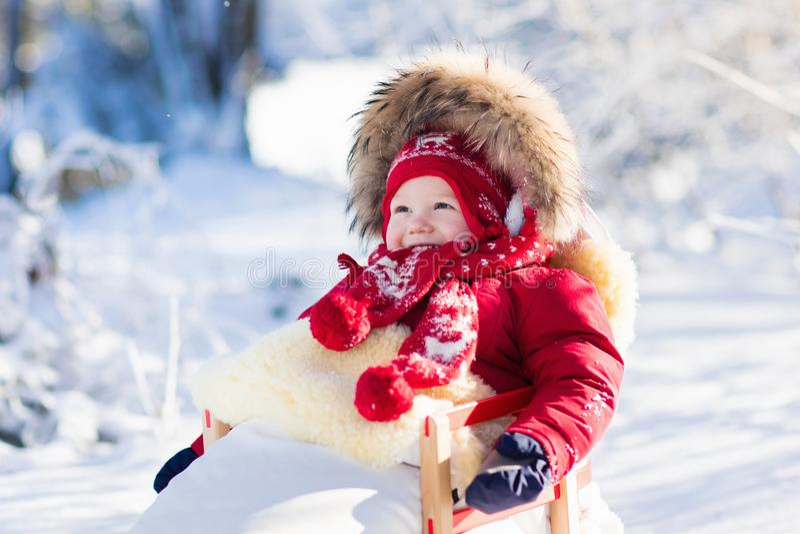 Divertimento della neve e della slitta per i bambini Bambino che sledding nel parco di inverno immagini stock