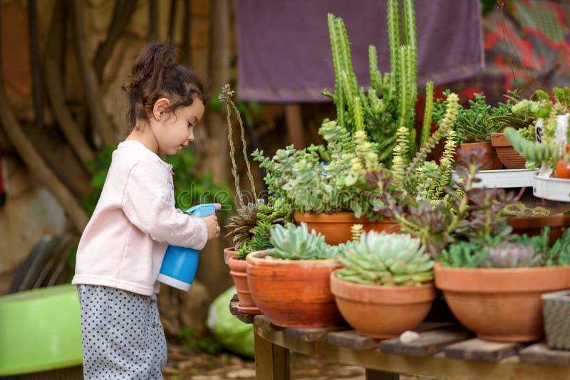 Divertimento di estate: Piccolo giardino d'innaffiatura della bella ragazza immagini stock libere da diritti