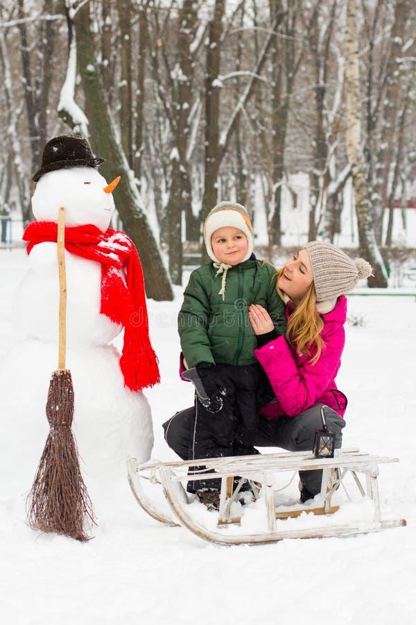 Divertimento di inverno con il pupazzo di neve in cappello e mamma e figlio rossi della sciarpa fotografie stock libere da diritti