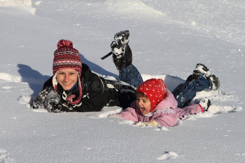 Divertimento di inverno: madre e bambino che giocano nella neve fotografia stock