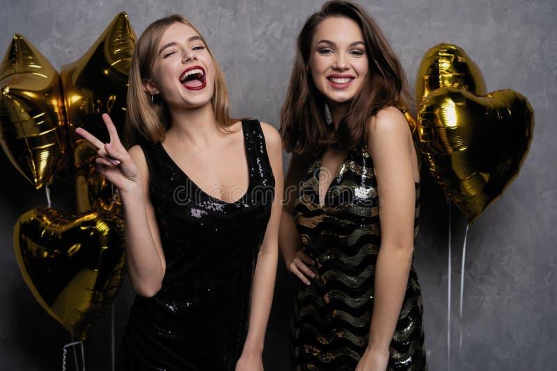 Divertimento do partido Meninas bonitas que comemoram o ano novo Retrato das jovens mulheres de sorriso lindos que apreciam a cel fotografia de stock