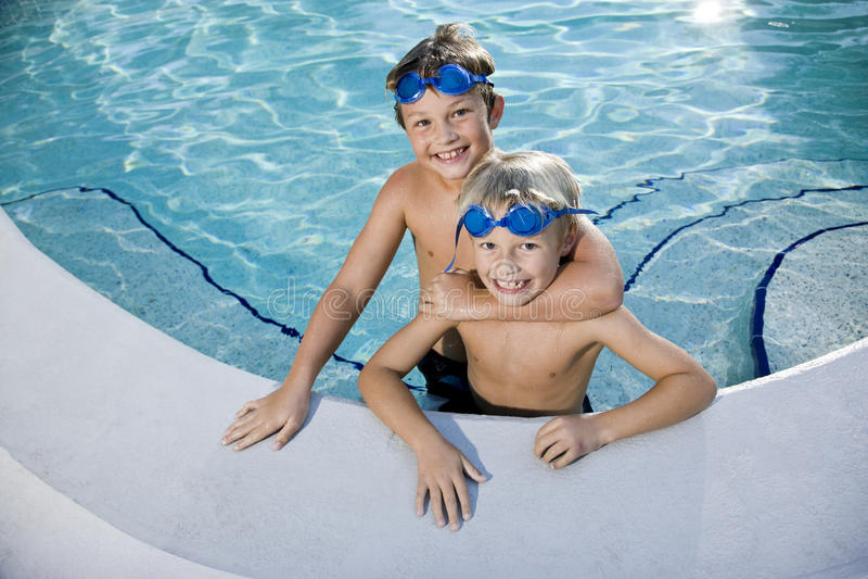 Divertimento do verão, meninos que jogam na piscina foto de stock