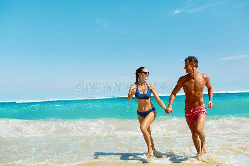 Divertimento dos pares na praia Povos românticos no amor que corre no mar fotografia de stock royalty free