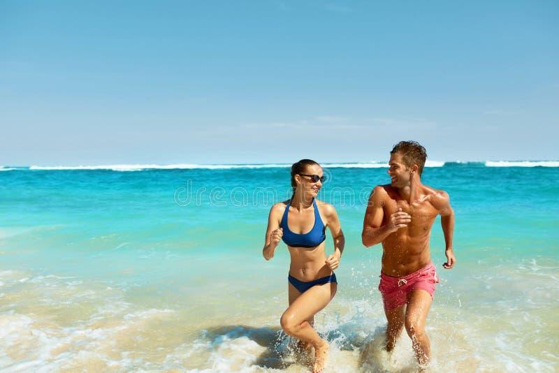 Divertimento dos pares na praia Povos românticos no amor que corre no mar imagens de stock