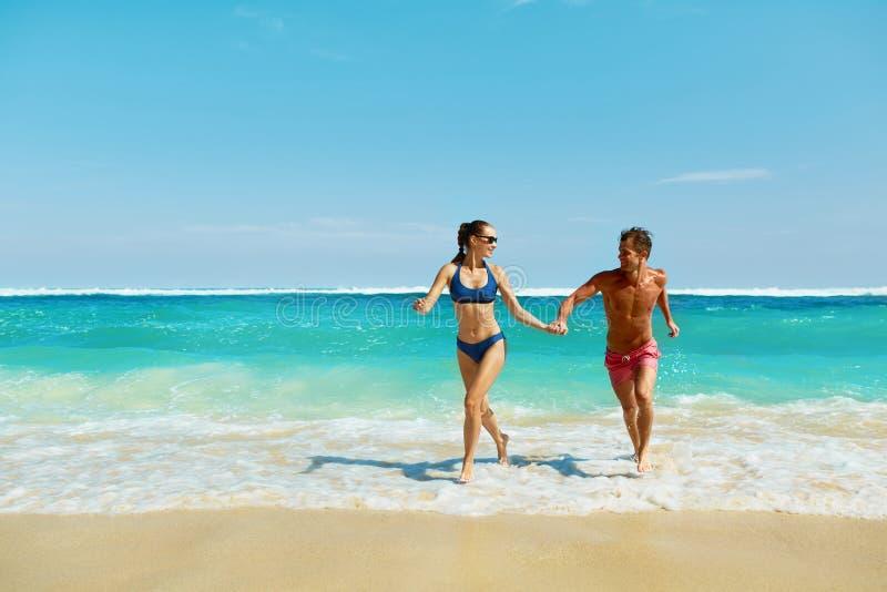 Divertimento dos pares na praia Povos românticos no amor que corre no mar imagem de stock royalty free