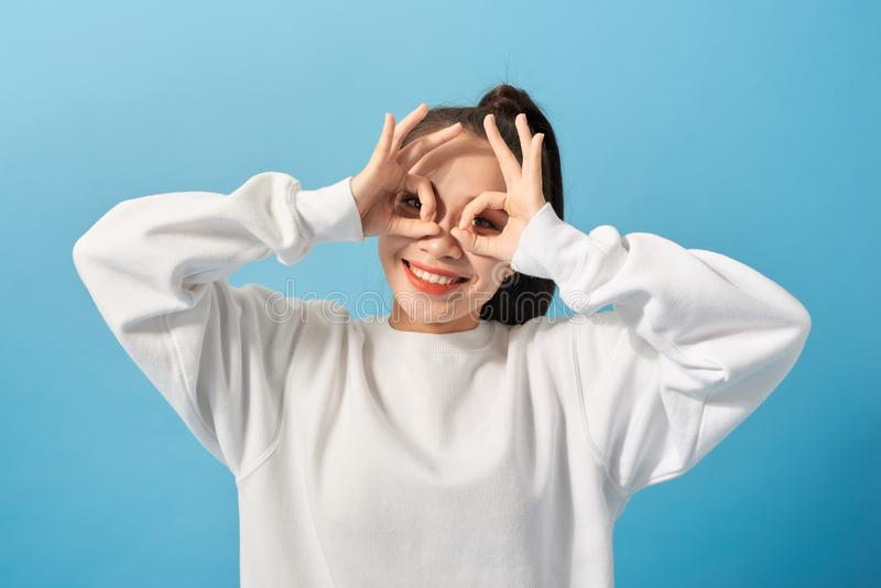 Divertimento e conceito dos povos - jovem mulher ou adolescente de sorriso que olham através dos vidros de dedo sobre claro - fun foto de stock royalty free