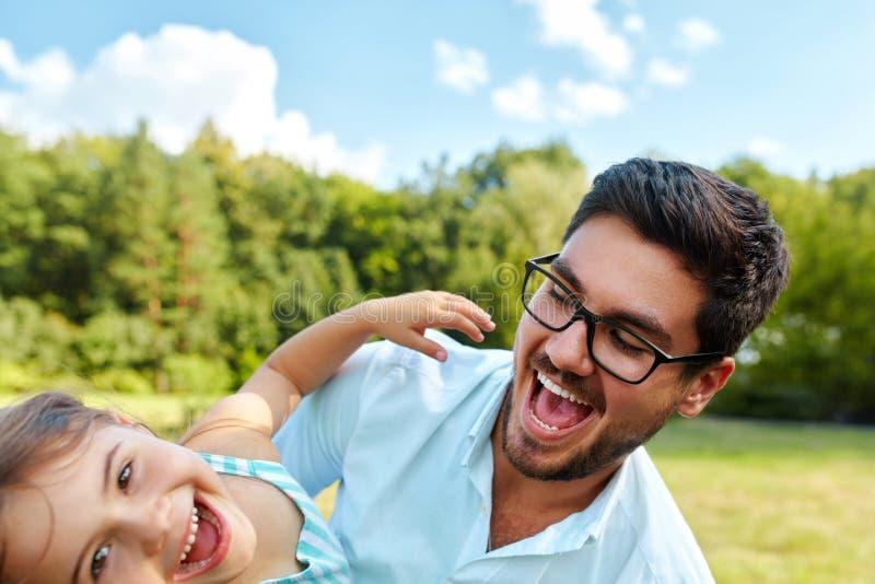 Divertimento felice di And Child Having del padre che gioca all'aperto Tempo della famiglia fotografia stock libera da diritti