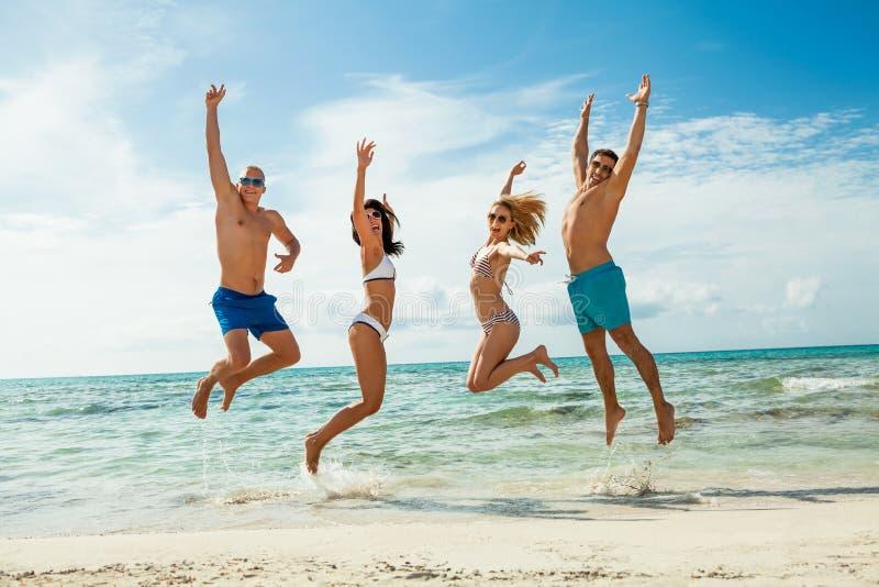 Divertimento feliz novo do havin dos amigos na praia fotografia de stock