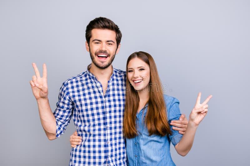 Divertimento insieme La coppia allegra gesturing i segni di pace al lig immagine stock libera da diritti
