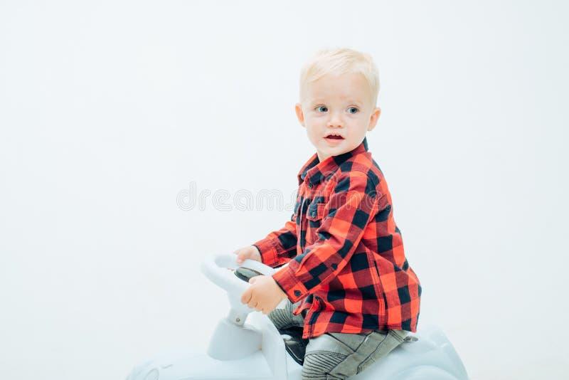 Divertimento ma cassaforte Poco bambino gode di di giocare nell'asilo Piccolo giro del bambino sull'automobile del giocattolo Bam fotografia stock libera da diritti