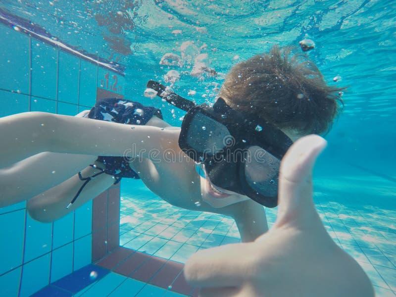 Divertimento novo subaquático do menino na piscina com óculos de proteção Divertimento das férias de verão fotografia de stock